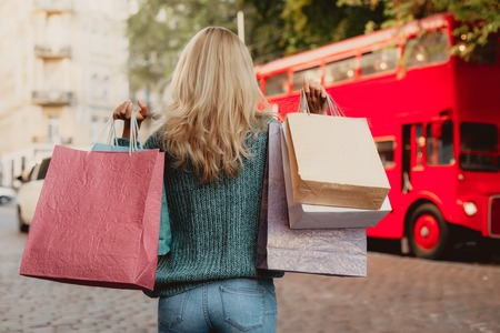 Sale season. Back view portrait of lady in sweater holding shopping bags