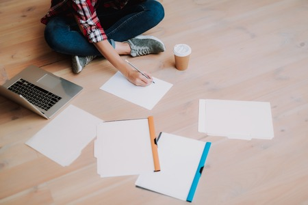 Cropped portrait of girl in jeans creating sketch while sitting on wooden floor with laptop, cup of coffee and folders