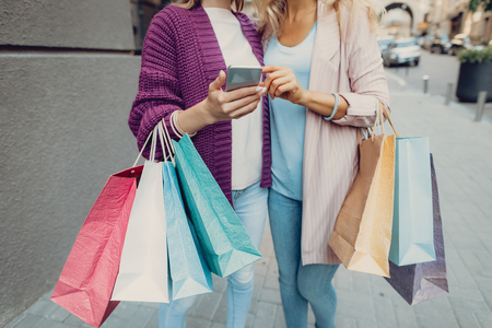 Cropped portrait of elegant girl holding cellphone while standing with mother outdoors. They carrying colorful shopping bags