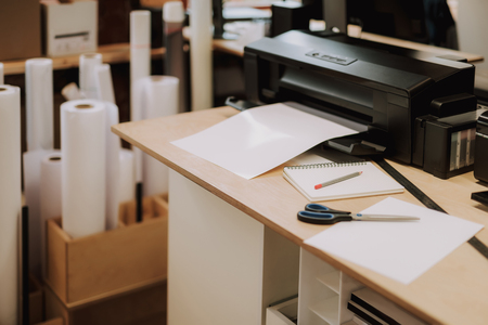 Office equipment, scissors, notebook with pencil, sheet of paper and ruler on wooden desk