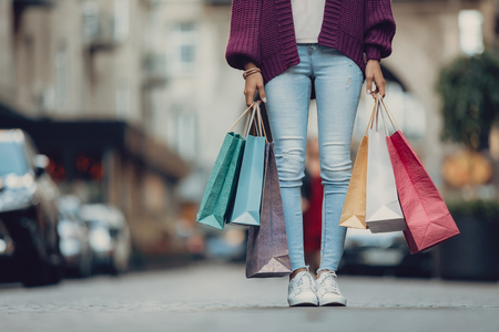 Big sale. Cropped portrait of stylish girl holding colorful shopping bags