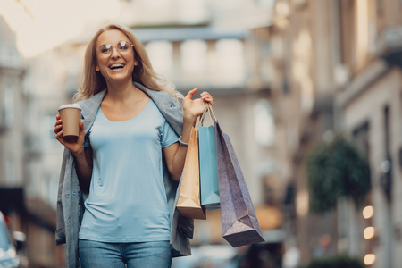 Waist up portrait of beautiful middle-aged lady in glasses holding cup of coffee and shopping bags. She is looking at camera and laughing Stock Photo