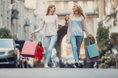 Full length portrait of beautiful girl and her mother holding cups of coffee and carrying shopping bags. They looking at each other and smiling Stock Photo