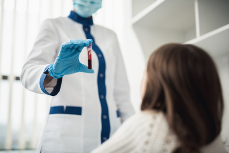 Professional facility investigations in healthcare system. Low angle waist up portrait of female laboratory worker showing test tube with blood to little girl