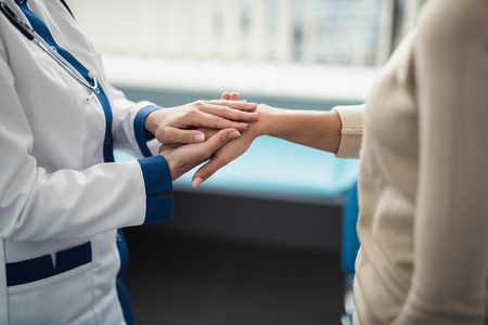 Concept of positive method of consultation in healthcare system. Close up portrait of doctor woman holding hands of young female while consulting Stock Photo