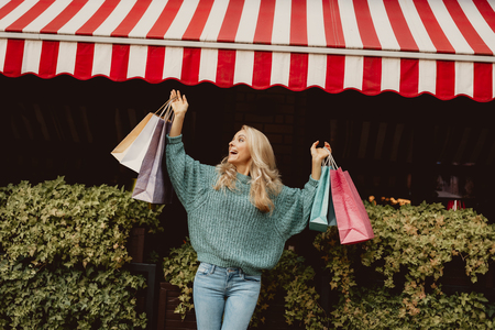 Portrait of beautiful lady in sweater raising colorful shopping bags. She is smiling Stock Photo