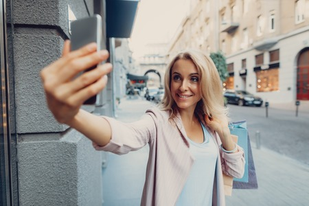 Waist up portrait of charming middle-aged lady taking photo with smartphone while holding shopping bags Stock Photo