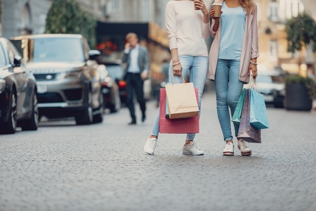 Cropped portrait of girl in jeans and her mother holding shopping bags and cups of hot drink