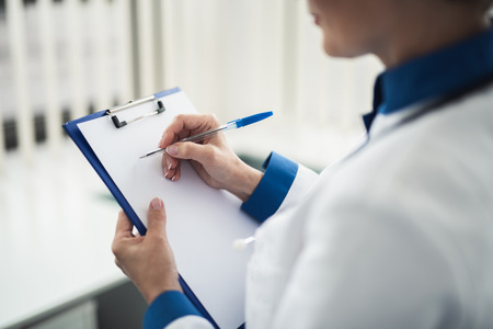 Concept of professional consultation in healthcare system. Back side close up portrait of female doctor writing on notes holder while standing in cabinet