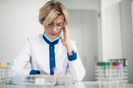 Professional tiredness in facility investigations. Waist up portrait of female laboratory worker having head ache while making notes in lab office