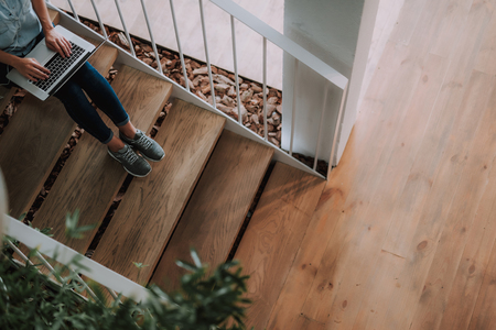 Cropped top view portrait of busy woman using notebook while sitting on wooden stairs Stock Photo