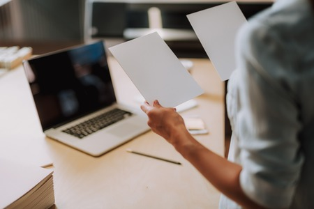 Close up of white templates for design in female hands. Woman standing near office table with laptop