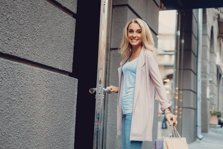Portrait of charming middle-aged lady with shopping bags standing on the street and holding boutique door handle. She is looking at camera and smiling