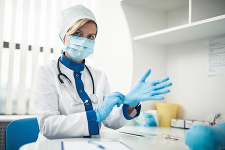 Professional laboratory investigations in healthcare system. Close up waist up portrait of lady doctor in medical uniform wearing gloves for making haemanalysis
