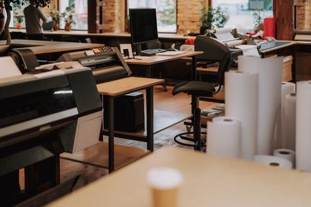 Cómodo lugar de trabajo con computadora negra en la mesa, rollos de papel e impresora