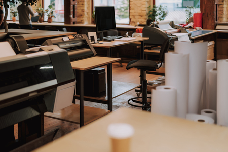 Comfortabele werkplek met zwarte computer op tafel, rollen papier en printer