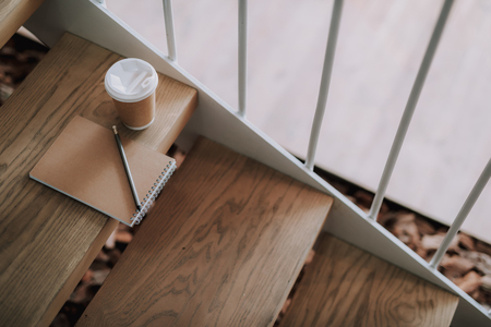 Close up of hot beverage and notepad on wooden stairs