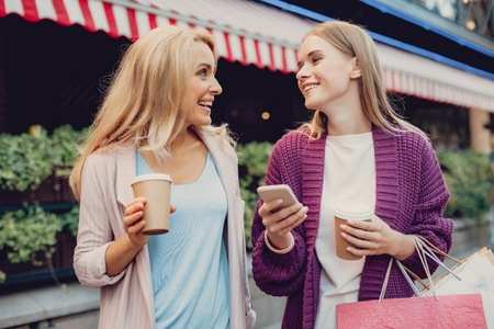 Waist up portrait of beautiful middle-aged woman with cup of coffee looking at her daughter and smiling. Lovely girl holding smartphone and shopping bags Stock Photo
