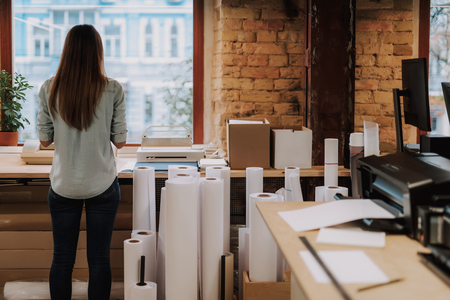Back view portrait of charming woman with long hair standing near rolls of paper and office desk