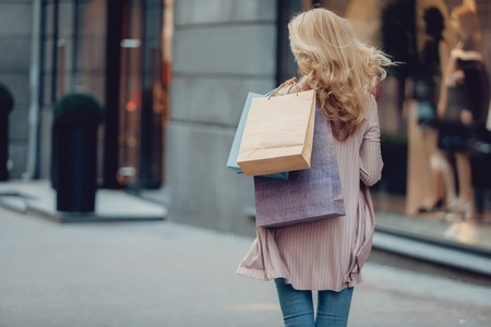 I am heading to the store. Back view portrait of middle-aged woman carrying colorful shopping bags