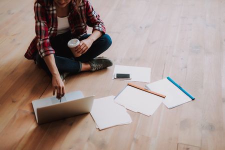 Cropped portrait of charming girl holding cup of coffee while sitting on wooden floor with notebook, smartphone and documents Stock Photo