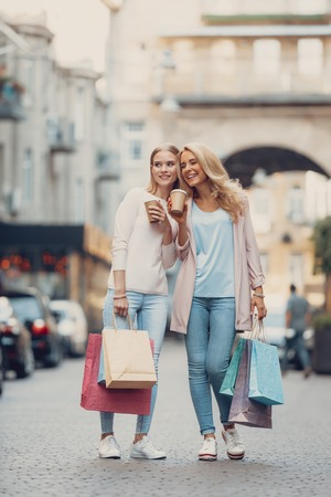 Full length portrait of beautiful girl and her mother holding shopping bags and cups of hot drink. They standing on the street and smiling