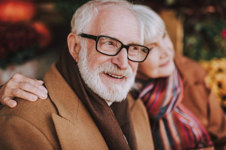 Close up portrait of stylish gentleman looking away and smiling while lady hugging him. Focus on male pensioner