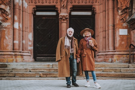 Full length portrait of stylish bearded man and his wife standing near old building. Lady in hat holding cup of coffee 스톡 콘텐츠