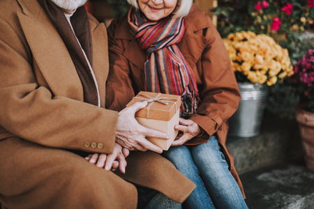 Cropped portrait of smiling old lady accepting gift box from loving husband. Pensioners holding hands while sitting on stairs