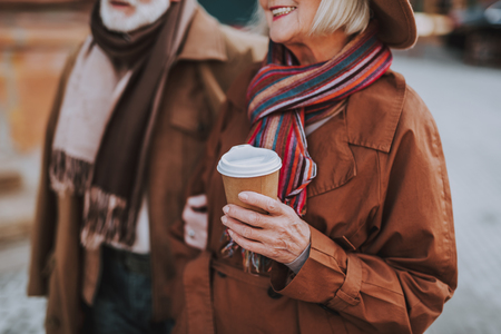 Cropped portrait of smiling elderly woman in hat holding cup of hot drink while spending time with husband outdoors. Focus on lady hand with beverage