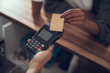 Hand of woman holding credit card and paying with it while putting elbow on the bar counter Imagens