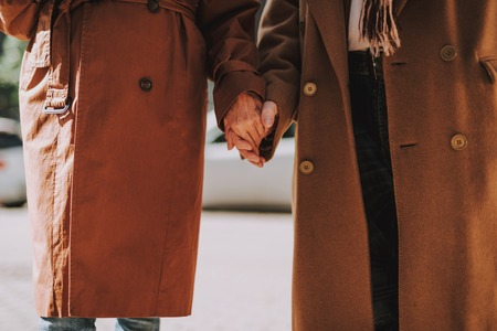 Cropped portrait of old gentleman and his wife sharing tender moment. They wearing coats Stockfoto