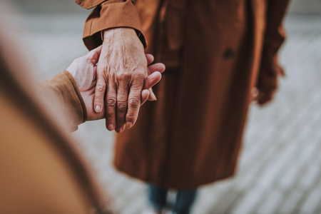 Close up of loving senior couple holding hands on the street