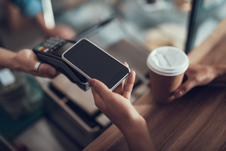 Careful progressive lady with manicure holding her smartphone over the credit card payment machine while using contactless payment system Imagens - 113208588