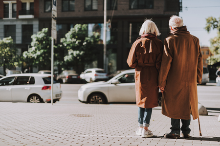 Back view full length portrait of old gentleman with cane and his wife standing on sidewalk. They wearing coats Imagens