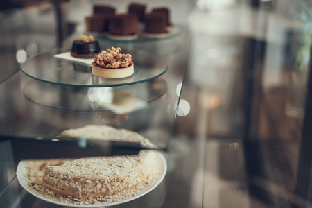 Tasty little patty cakes placed on the plates in glass case of popular cafe Imagens