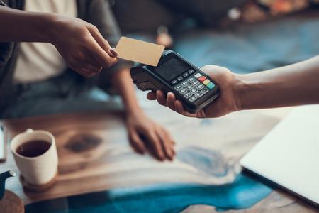 Handen van cafébezoeker die creditcard vasthoudt en naar de kaartbetaalmachine brengt