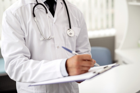 Doctor in white uniform standing with stethoscope on his neck and making notes on the clipboard