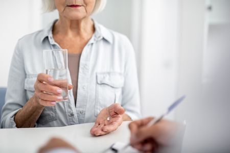 Calm elderly lady visiting her practitioner and holding a glass of water while taking pills