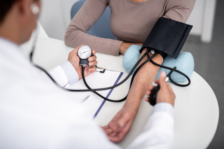 Female patient sitting at the table and general practitioner measuring her blood pressure