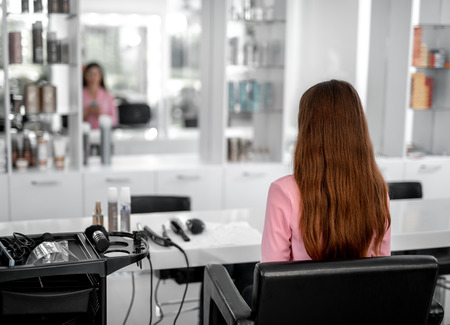 Back view of lady looking in the mirror while being in the beauty salon. Copy space on left side