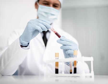 Ruhiger konzentrierter Arzt, der alleine sitzt und vorsichtig Reagenzglas mit Blutprobe aus dem Röhrchenständer nimmt