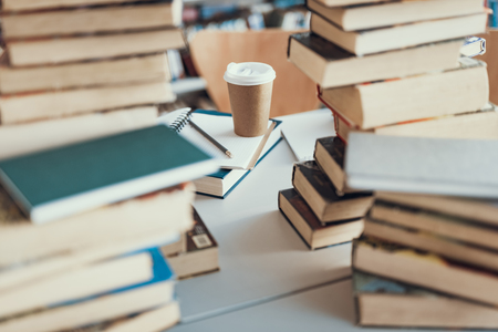 Horizontal photo of the carton cup of coffee surrounded by piles of books and notebooks