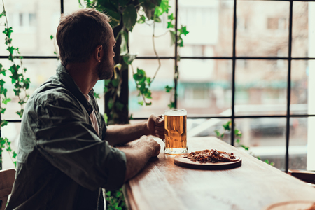 Side view portrait of young gentleman holding mug of beer while sitting at the table with snacks