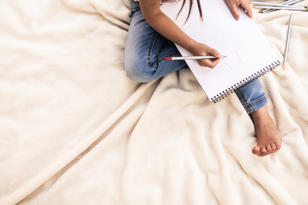 Top view of girl sitting on bed with light bedspread. She drawing something on album sheet