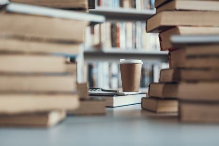 Piles of books on the table with a carton cup of coffee in the middle