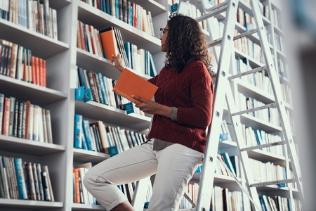 Young curly student smiling while standing on the step ladder and carefully taking necessary books from the shelf