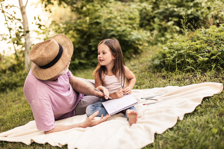 Man in straw hat explaining something to little girl while sitting in summer nature 스톡 콘텐츠 - 114088048