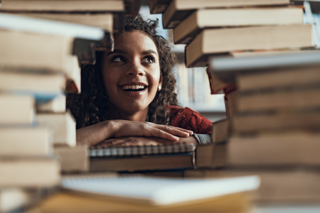 Positive young lady feeling excited and smiling while looking up and sitting in front of the pile of books