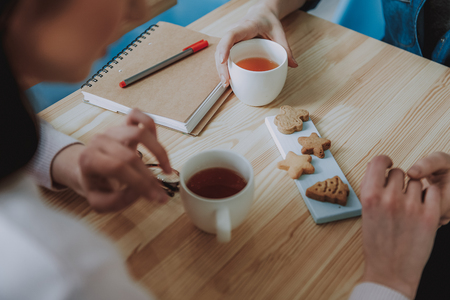 Plose up of nice women sitting in the cafe while enjoyign tea with cookies Stock Photo